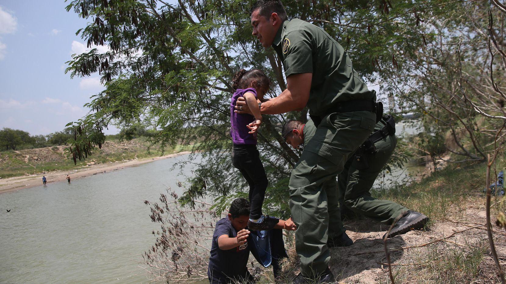 Un agente de la Patrulla Fronteriza ayuda a migrantes de El Salvador a salir del Río Grande en la zona del sur de Texas. (GETTY IMAGES/JOHN MOORE)