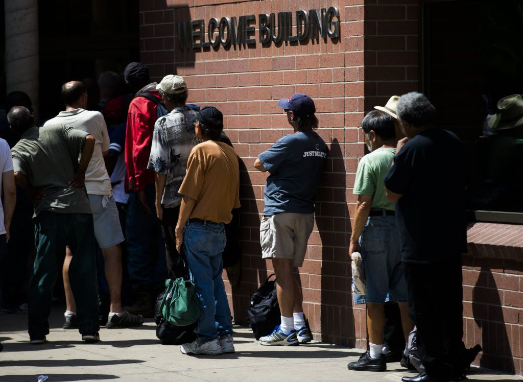 People waited in line at the welcome building inside The Bridge Homeless Recovery Center during June.  (Ashley Landis/Staff Photographer)