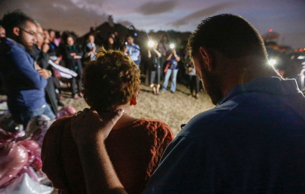 Nicole and Scott Snyder bow their heads in prayer at a vigil for Sherin Mathews in Richardson, Texas Friday night, October 20, 2017. The Snyder's are the founders of the Finding Sherin Mathews Facebook page and helped organize the vigil. The vigil was held in an alley near her parents house where her father said he left her almost three weeks ago.