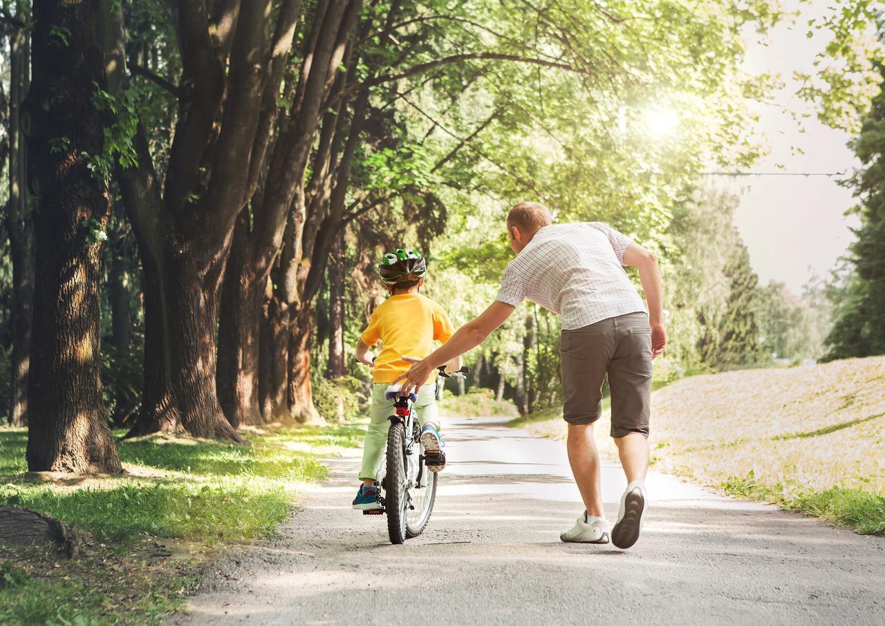 Un padre ayuda a su hijo aprender a usar una bicicleta.(GETTY PHOTOS)