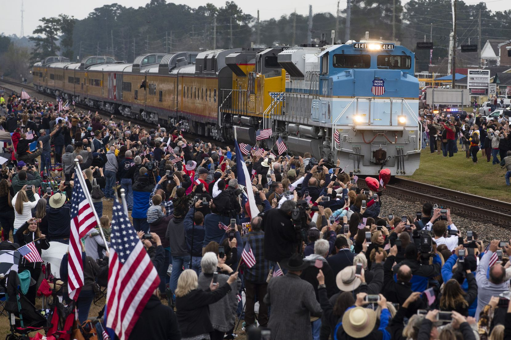 Mourners watch as a train carrying the remains of former President George H.W. Bush in Magnolia, Texas on Wednesday, December 6, 2018. The train traveled along the Union Pacific Corp. rail line from Spring to College Station. Bush died on November 30, 2018. (Shaban Athuman/The Dallas Morning News)
