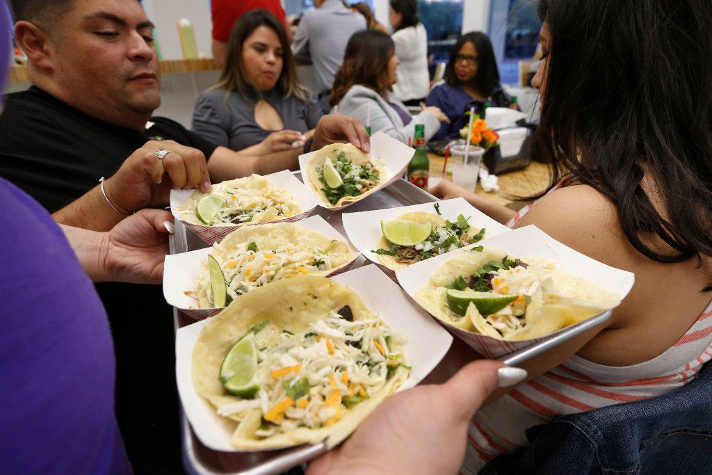 Eric Montoya (left) and Tina Hernandez (center) pick from the tacos at Salsa Limon in Dallas on March 16, 2017.  (Nathan Hunsinger/The Dallas Morning News)