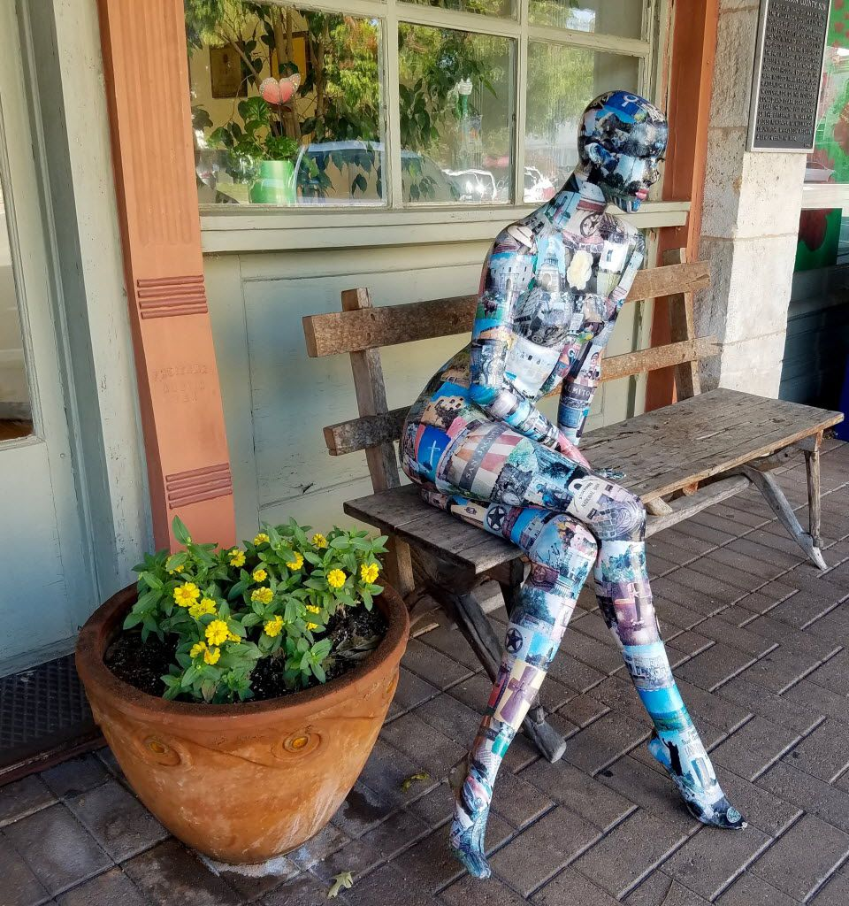 A decoupaged sculpture of a woman on a bench sits outside the office of the twice-weekly Williamson County Sun in Georgetown.