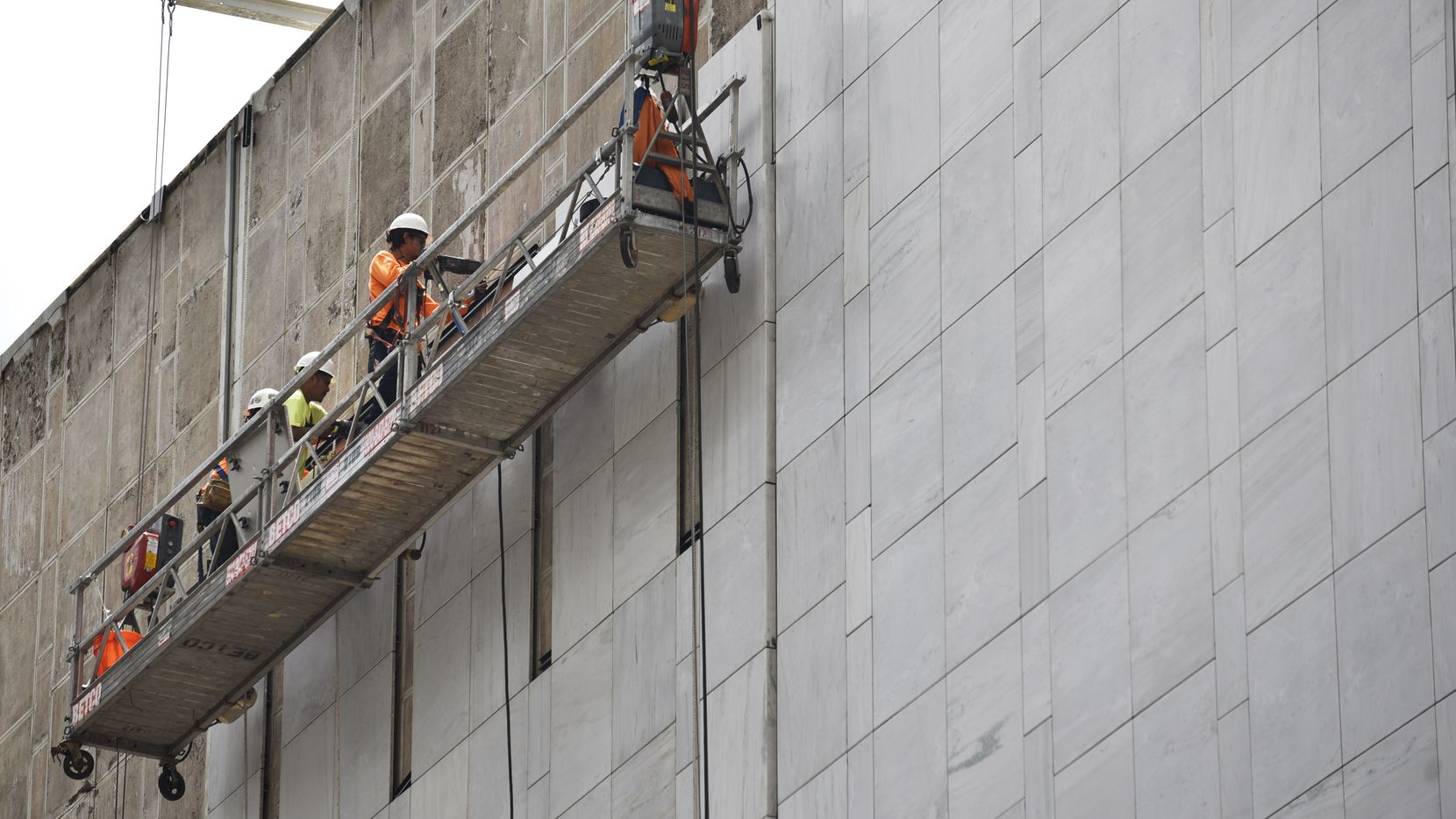 Construction workers use a scaffold to install marble on the First National Bank building in downtown Dallas.