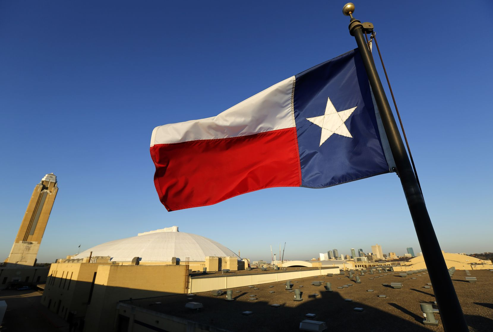 The Texas flag waves above the Pioneer Tower (from left), Will Rogers Memorial Coliseum and Fort Worth skyline during the Fort Worth Stock Show and Rodeo, Wednesday, January 30, 2019.