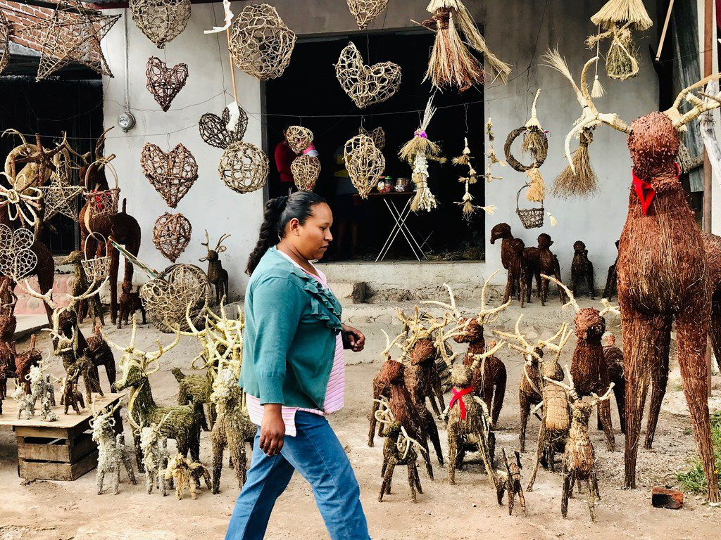 """Olivia Carranza walks by a shop selling reindeer made of straw in the town of Saucedo on September 30th. She's not emigrating like so many others. """"I love Mexico because somehow it gives me enough to feed my family,"""" she says."""