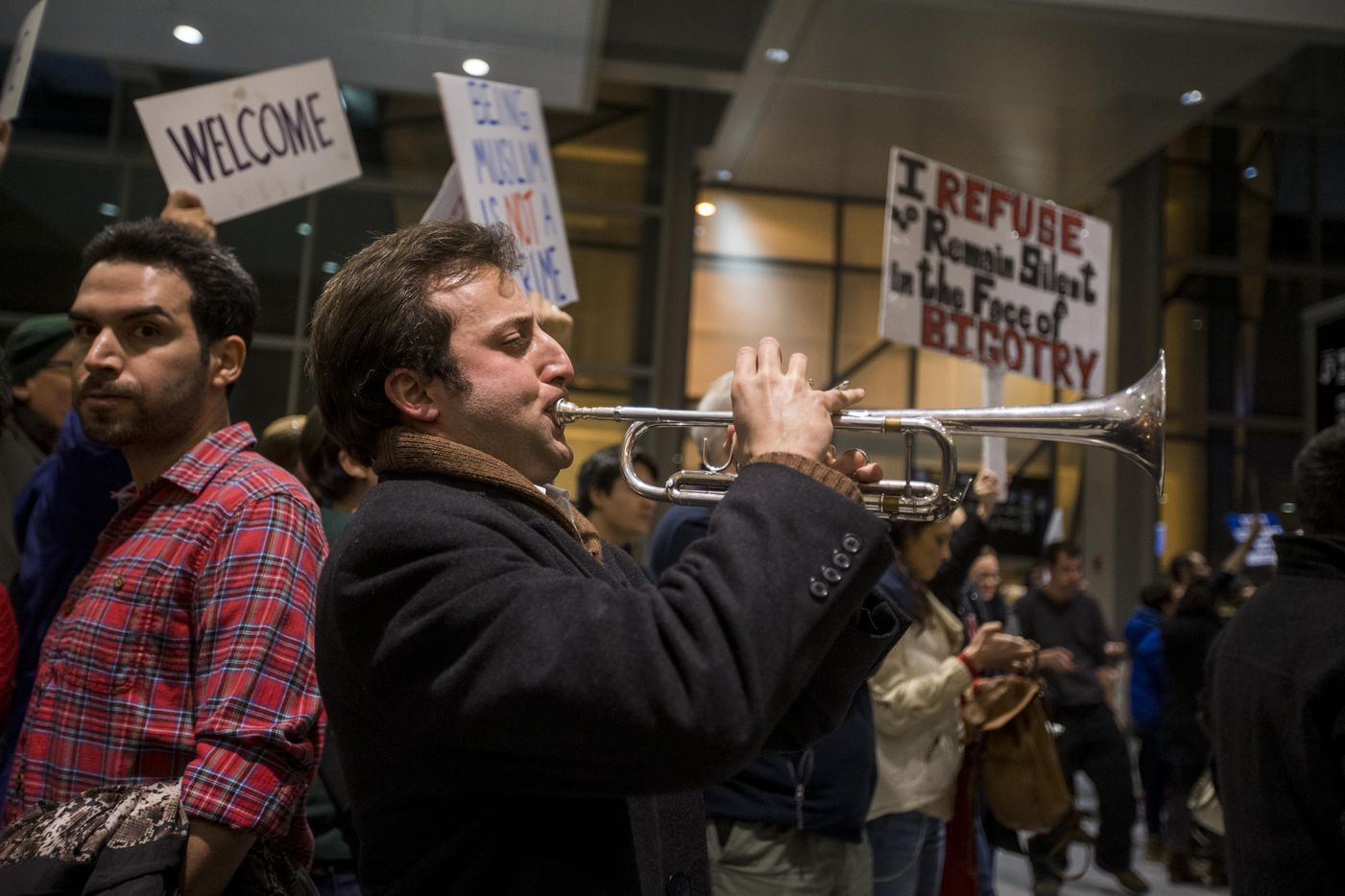 "A protestor plays ""This Land Is Our Land"" on a trumpet during a demonstration against the new ban on immigration issued by President Donald Trump at Logan International Airport on January 28, 2017 in Boston, Massachusetts."