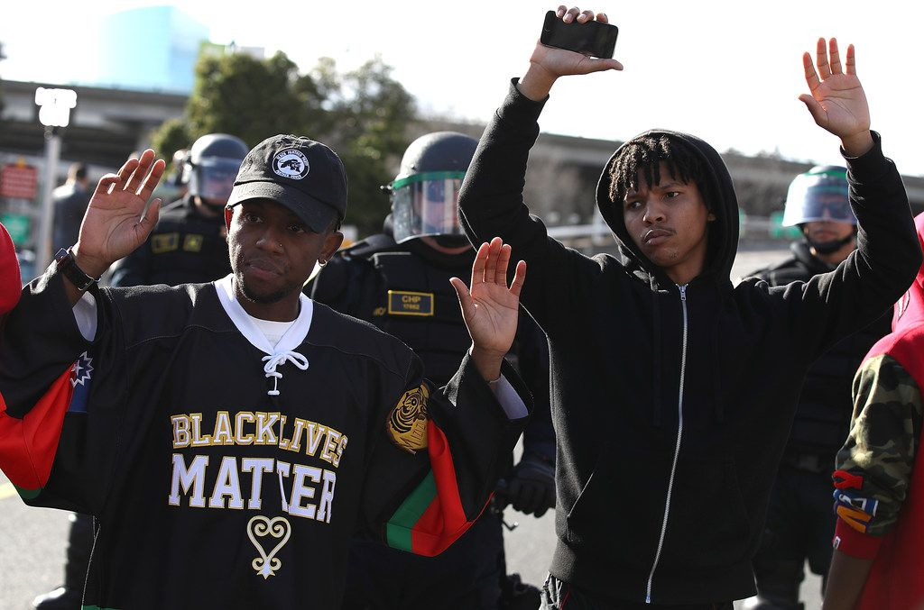 Black Lives Matter protesters stand with their hands up in front of California Highway Patrol officers as they block an entrance to Interstate 5 during a demonstration on March 23, 2018 in Sacramento, California.  For a second day, dozens of protesters marched through Sacramento to demonstraate against the Sacramento police department after two officers shot and killed Stephon Clark, an unarmed black man, in the backyard of his grandmother's house following a foot pursuit on Sunday evening.