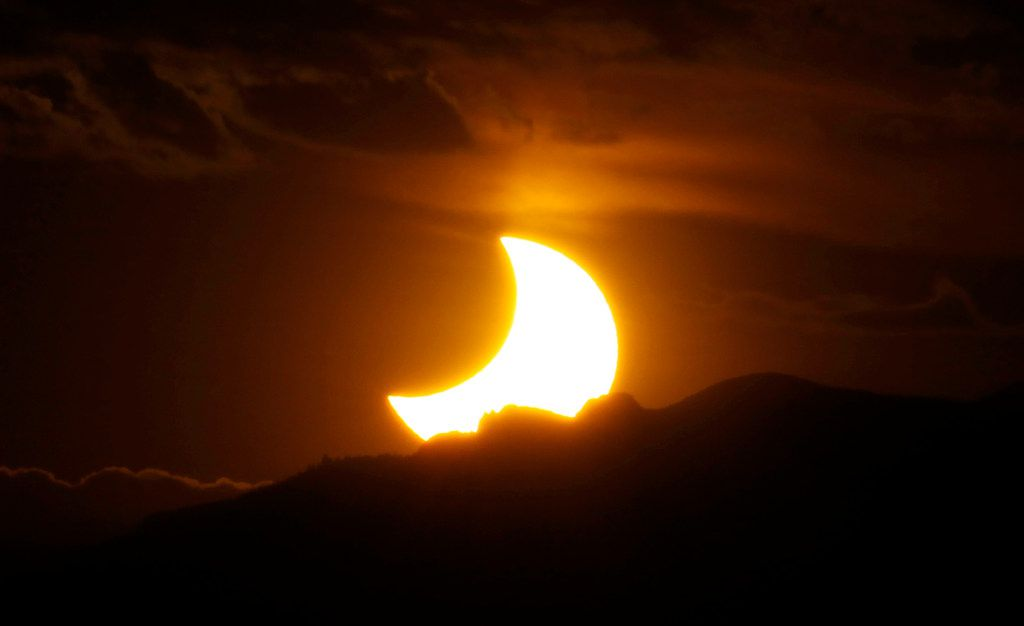 On May 20, 2012, a partial solar eclipse was seen from downtown Denver as the sun set behind the Rocky Mountains.