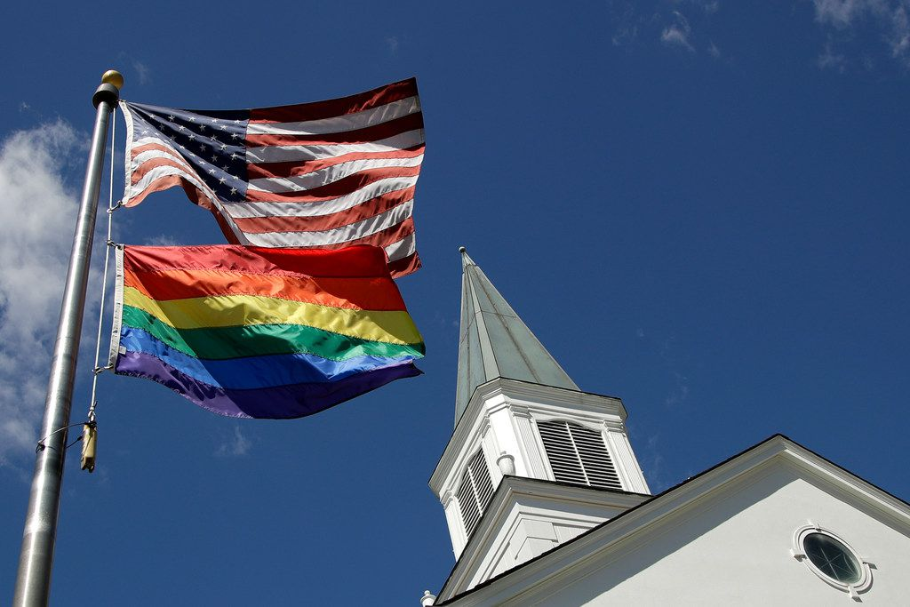 A gay pride rainbow flag flies along with the U.S. flag in front of the Asbury United Methodist Church in Prairie Village, Kan., on April 19, 2019.