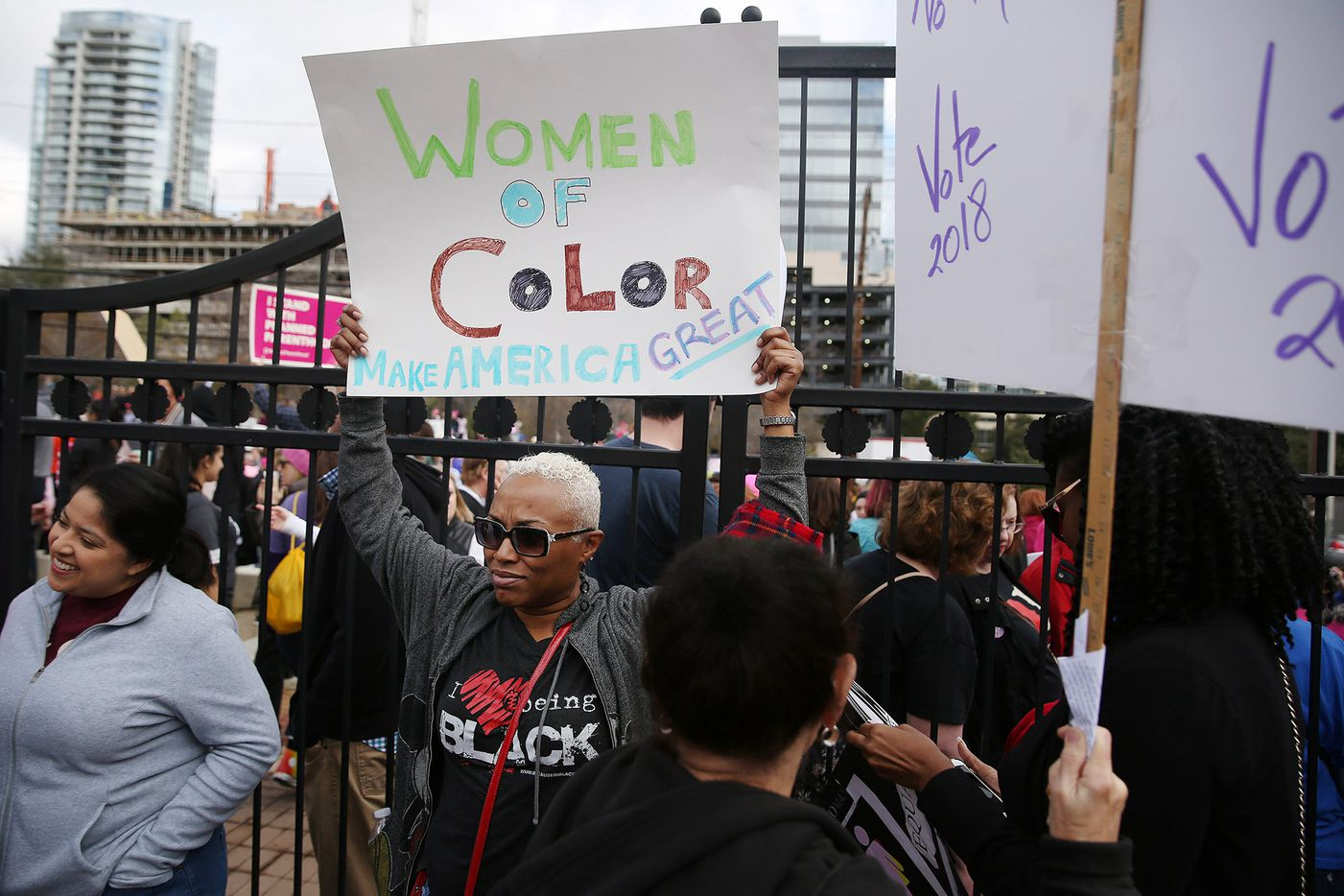 Julianna Taylor, of Dallas, holds up a sign at Pike Park before the rally portion of the Dallas Women's March in Dallas Saturday.