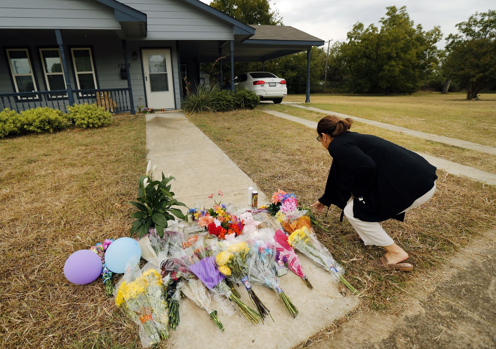 Anastasia Gonzalez of Burleson left flowers on the front sidewalk of Atatiana Jefferson's home on East Allen Avenue in Fort Worth. In the wake of Fort Worth officer Aaron Dean shooting and killing Jefferson in her home, people have been leaving flowers at a memorial.  (Tom Fox/Staff Photographer)