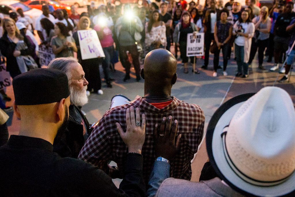 Clergymen laid hands on Dane Felicien, a family friend of Botham Shem Jean, as he spoke Sept. 7 during a vigil for Jean outside Jack Evans Police Headquarters.
