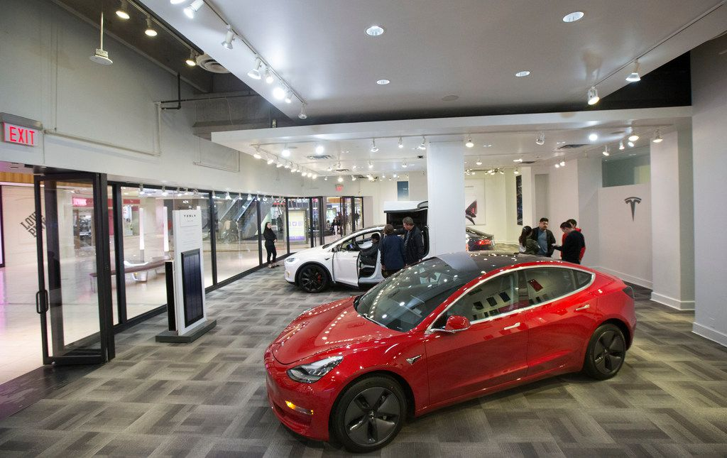 Shoppers speak with Tesla representatives while others explore the electric vehicles inside the Tesla showroom at Galleria Dallas in Dallas on Monday, January 14, 2019. According to Tesla's website, it produces all of its vehicles at its factory in Fremont, California.