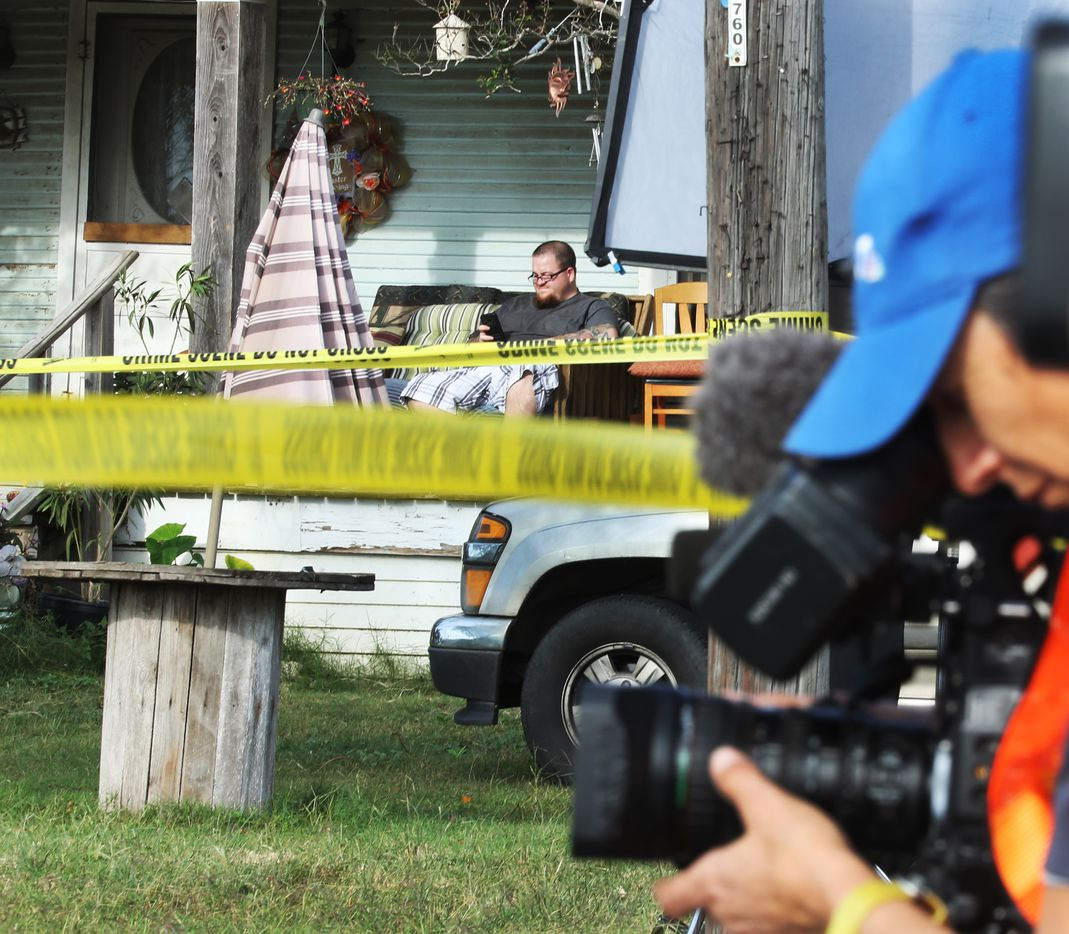 As members of the media record the scene, a resident of Sutherland Springs surveys the situation from his porch.