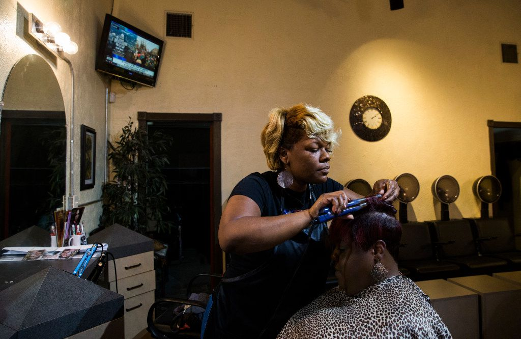 Shannon Gilstrap curls Ericka Davison's hair at Rampage Beauty and Barber Salon across the street from Fair Park on Friday, January 20, 2017 on Parry Avenue in Dallas.