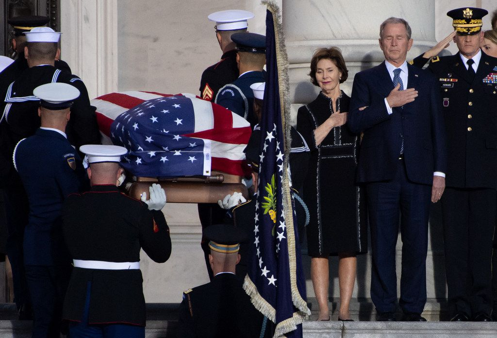 Former US President George W. Bush, and former First Lady Laura Bush, watch as the casket containing the remains of former  President George H.W. Bush arrive at the U.S. Capitol during a State Funeral in Washington, DC, December 3, 2018.