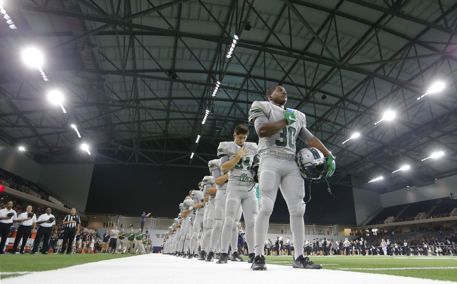Reedy's Justin Gipson (30) and team during the playing of the National Anthem before playing against Independence High School in the first high school football game at The Star in Frisco on Saturday, August 27, 2016. (Vernon Bryant/The Dallas Morning News)