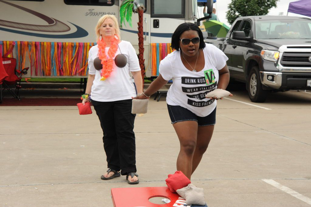 Friends play corn hole at the Jimmy Buffett tailgate party at Toyota Stadium in Frisco, TX on May 30, 2015.