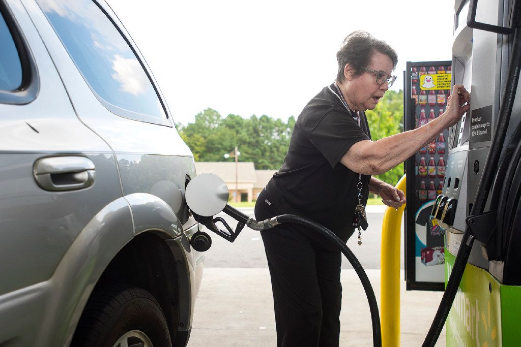 Dollie Chase inserts her card to pay for gas at a Walmart in Tyler, Texas, on Thursday, Aug. 31, 2017.  It's getting harder to fill gas tanks in parts of Texas where some stations are out of fuel and pump costs are spiking in the aftermath of Harvey. (Chelsea Purgahn/Tyler Morning Telegraph via AP)