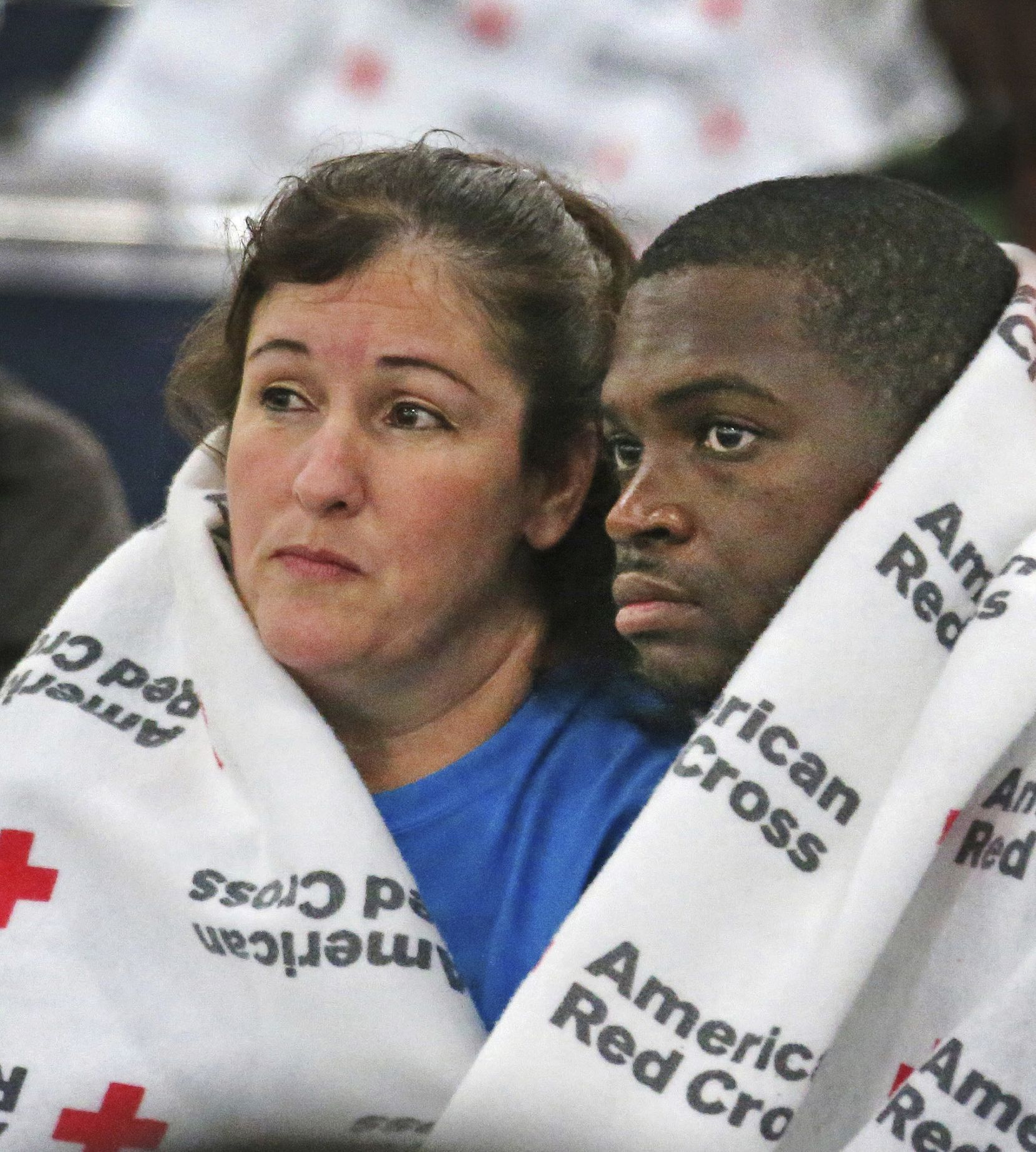 Displaced South Houston residents Oralia Guerra and Diamond Robinson huddle together to stay warm underneath Red Cross blankets at the George Brown Convention Center in Houston on Monday, Aug. 28, 2017, in the wake of Tropical Storm Harvey.