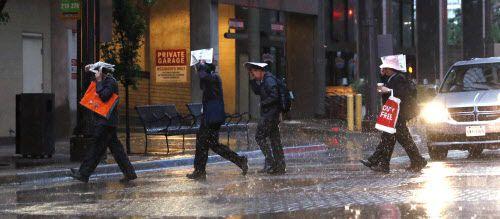 Peatones cruzan Main Street, en el centro de Dallas, durante la lluvia de la mañana del lunes.