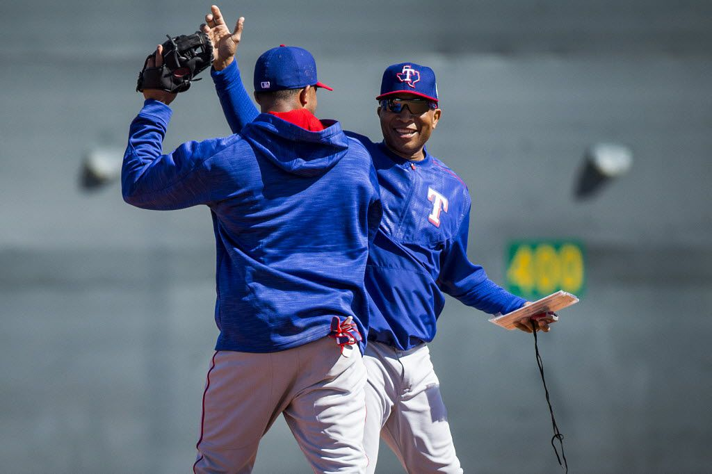 Texas Rangers third base coach Tony Beasley (right) high fives shortstop Elvis Andrus after he made a play in a fielding drill during a spring training workout at the team's training facility on Wednesday, Feb. 24, 2016, in Surprise, Ariz. (Smiley N. Pool/The Dallas Morning News)