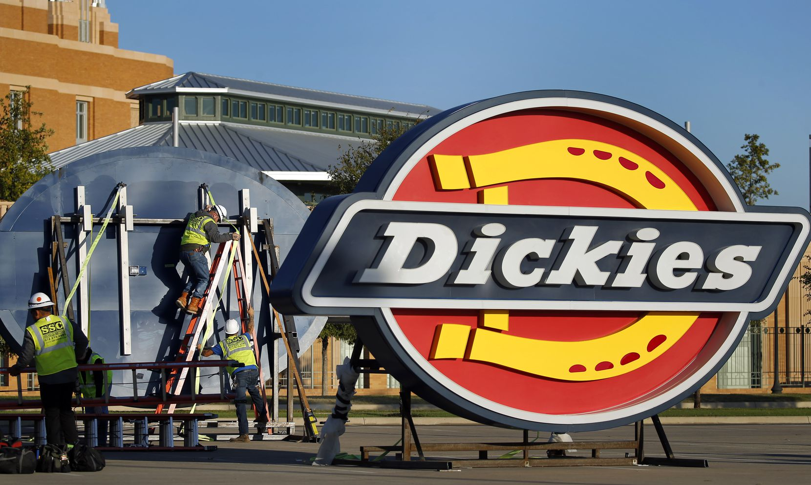 A crew from SSC Signs and Lighting preps four large Dickies logos to be lifted into place atop the new Dickies Arena in Fort Worth on Oct. 18, 2019.