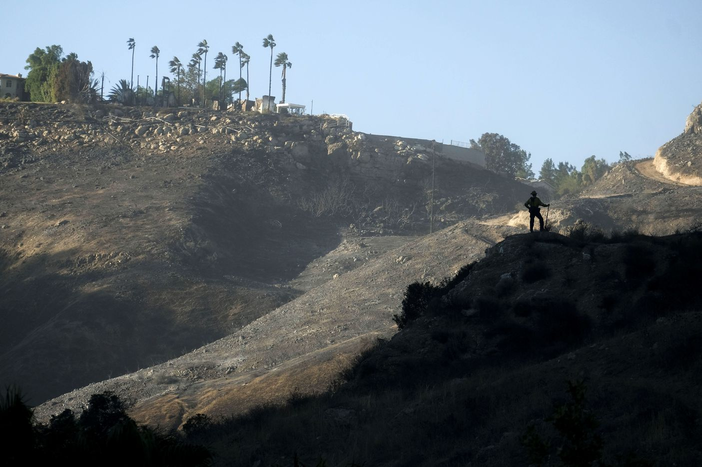 A firefighter is silhouetted against a burned area in West Hills, Calif., Nov. 11, 2018.