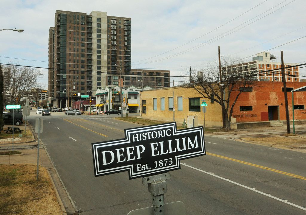An Historic Deep Ellum street sign on Hall Street welcomes visitor. The tall building in the background is the Case Building, a 17-story residential high-rise.