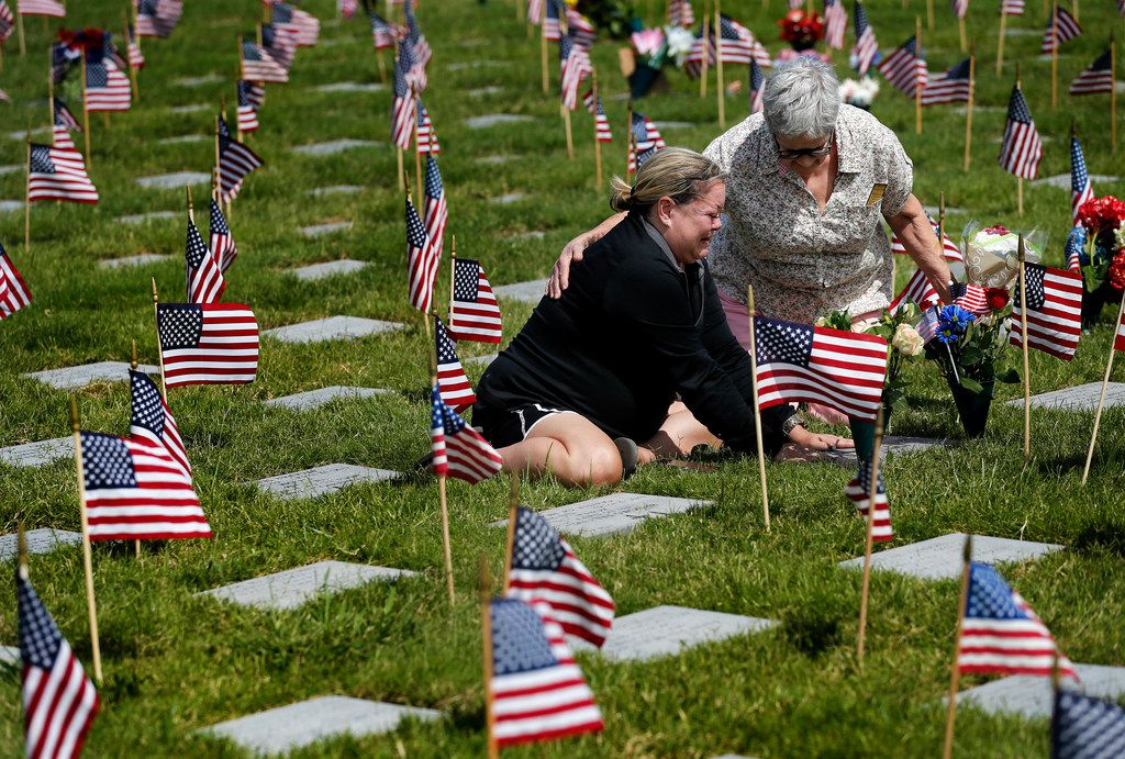 Cynthia Reeves of Fort Worth (right) came over to console Samantha Mote Bingham of Arlington who was overcome with emotion while visiting the grave of her parents during Monday's ceremony at Dallas-Fort Worth National Cemetery. Her father, Robert Mote, an Air Force 1st Lt. who served in the Korean War, is buried there with his wife Joy.