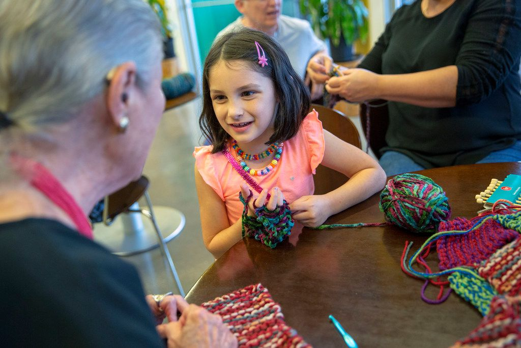 At Spreading the Warmth's monthly Knit Night, Sophie McKinney, 6, asks Arlene Leibs how many scarves she has made.