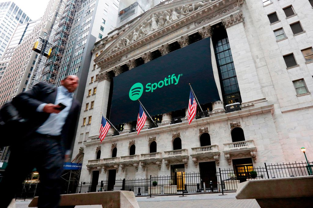 In this April 3, 2018, file photo, a Spotify banner adorns the facade of the New York Stock Exchange. The music streaming platform has removed R. Kelly's music from its playlists.