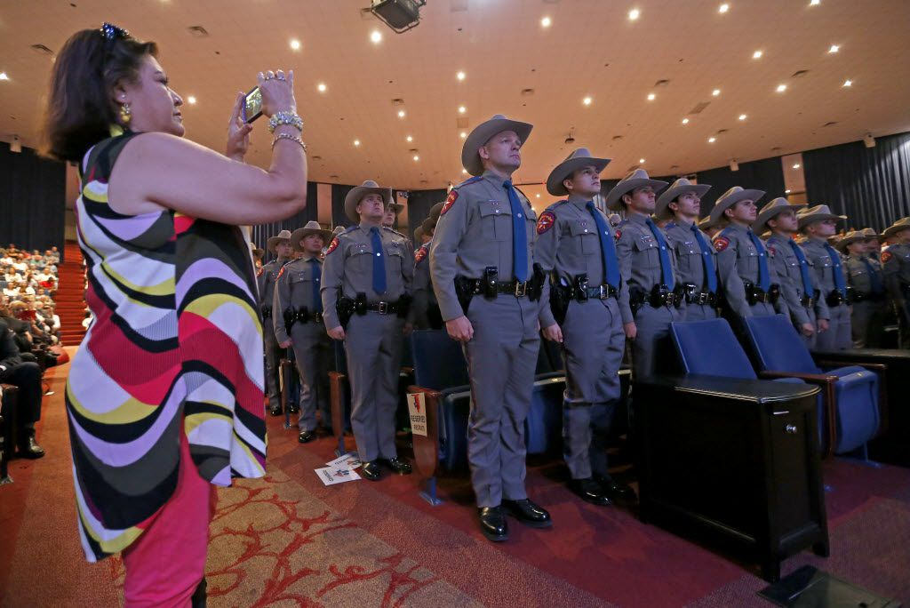 Janie Pierce (left) uses her cell phone to photograph members of the 155th trooper training class during the 155th trooper training class graduation ceremony at Shoreline Church on Friday, June 17, 2016, in Austin, Texas. Texas Department of Public Safety has the highest number of Hispanic trooper graduates at any time over the last decade and currently the classes of this year are about 40 percent Hispanic.