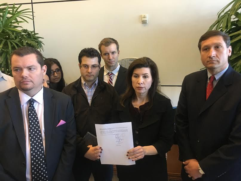 Angela Hunt, center, holds a copy of the Freedom of Information Act lawyers submitted during a press conference Sunday.