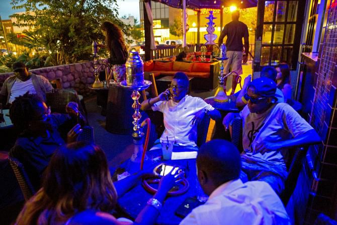 Friends hang out at Kush Mediterranean Grill & Hookah Bar on Lower Greenville. Smoking a hookah is trendy among the young, but many have no idea they are inhaling a cigarette pack's worth of nicotine and tar in a single session, says researcher Thomas Eissenberg.