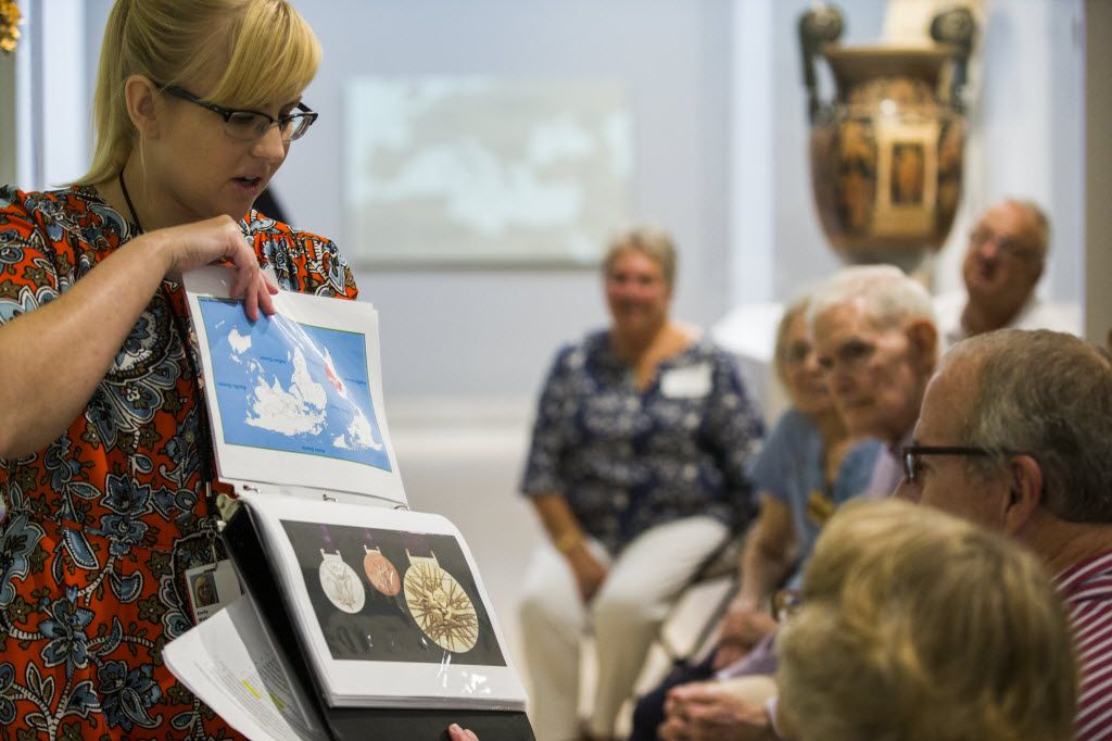 Emily Wiskera, manager of access programs, shows photos of Olympic medals during a presentation about ancient Greece as part of the Dallas Museum of Art's Meaningful Moments Program for individuals with early stages of dementia.