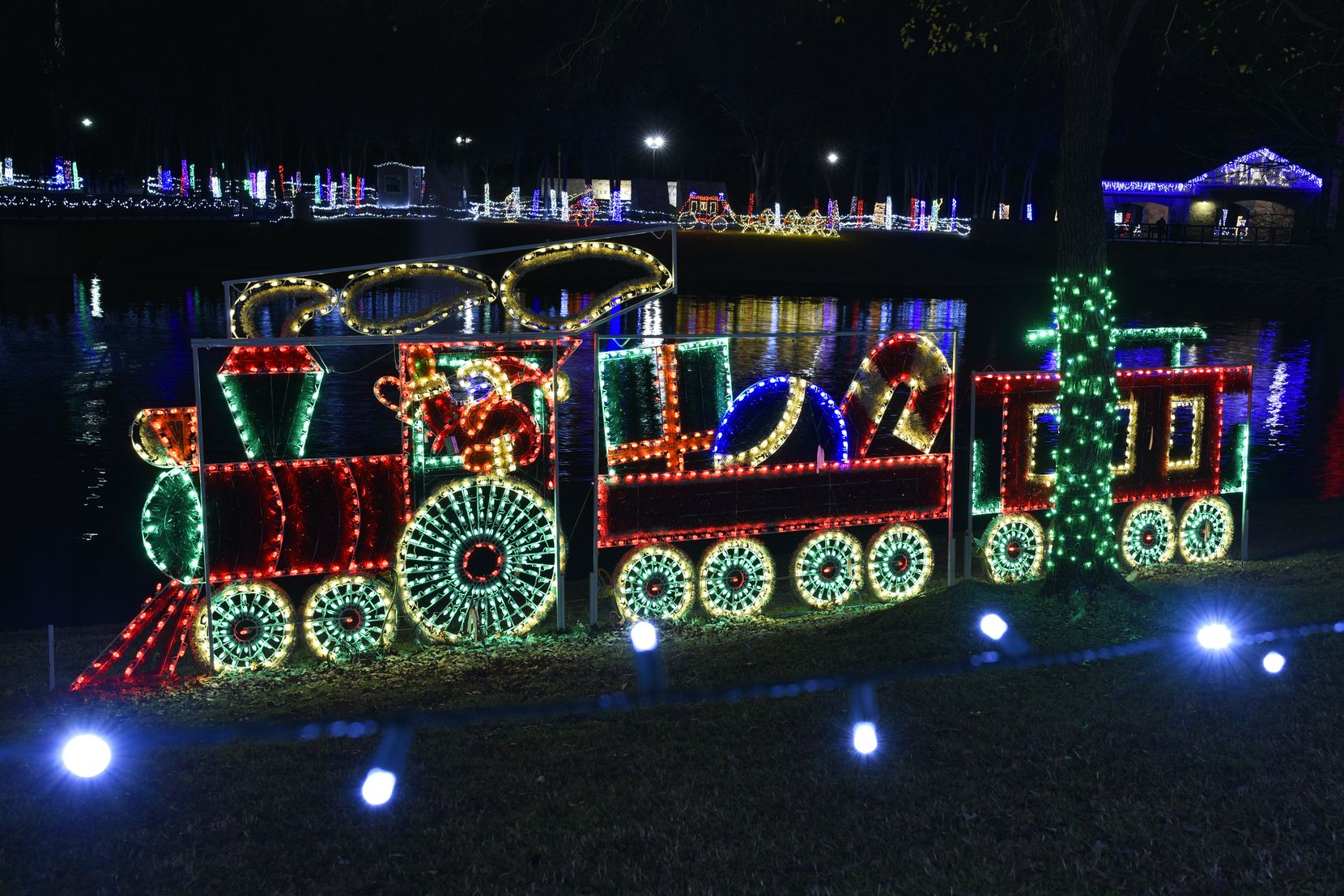 A Santa Claus train and other Christmas-themed light displays decorate the banks of Delaware Creek in Centennial Park in Irving.