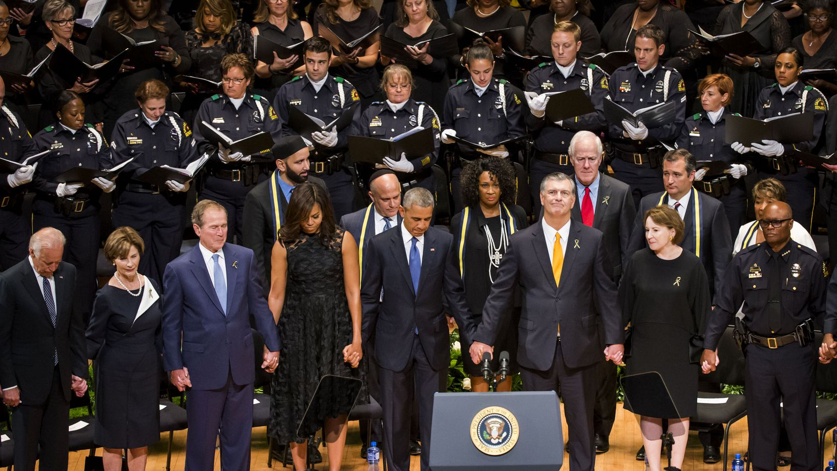President Barack Obama joins hands with Dallas Mayor Mike Rawlings and other dignitaries during an interfaith memorial service at the Morton H. Meyerson Symphony Center in Dallas for the five law enforcement officers killed last week. In the photo, from left, are Vice President Joe Biden, former first lady Laura Bush, former President George W. Bush, First Lady Michelle Obama, President Barack Obama, Dallas Mayor Mike Rawlings and his wife, Micki, and Dallas police chief David Brown.