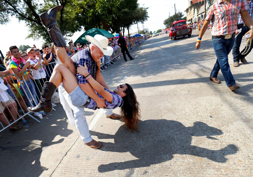 Alex Flores, of Roundup Saloon Dancers, dips country western dance partner Ray Govender of Dallas during the parade.