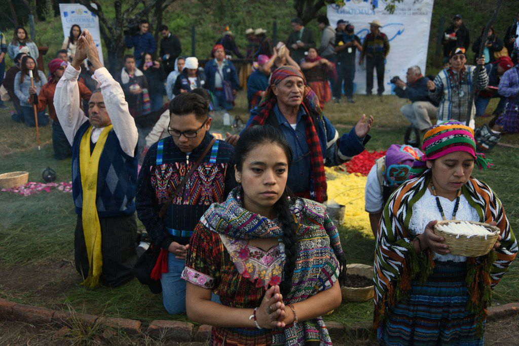 Mayan indigenous people celebrate a ceremony marking the 21st anniversary of the signing of the peace in Guatemala after 36 years of civil armed conflict (1960-1996), at the archaeological site of Kaminal Juyu in Guatemala City on December 29, 2017.