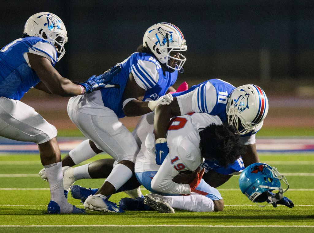 Skyline wide receiver Arabia Bradford (19) is tackled by Duncanville defensive lineman Kevon Ivy (10) and linebacker Amari Wynn (52) during the first quarter of a high school football game between Skyline and Duncanville on Friday, October 4, 2019 at Panther Stadium in Duncanville. (Ashley Landis/The Dallas Morning News)