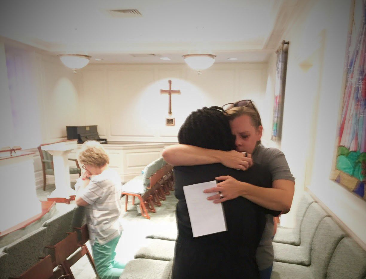 Arlene Williams, in black dress, hugs an unidentified woman in the chapel of Baylor University Medical Center. The woman is the wife of a Dallas police officer who was working Thursday night.