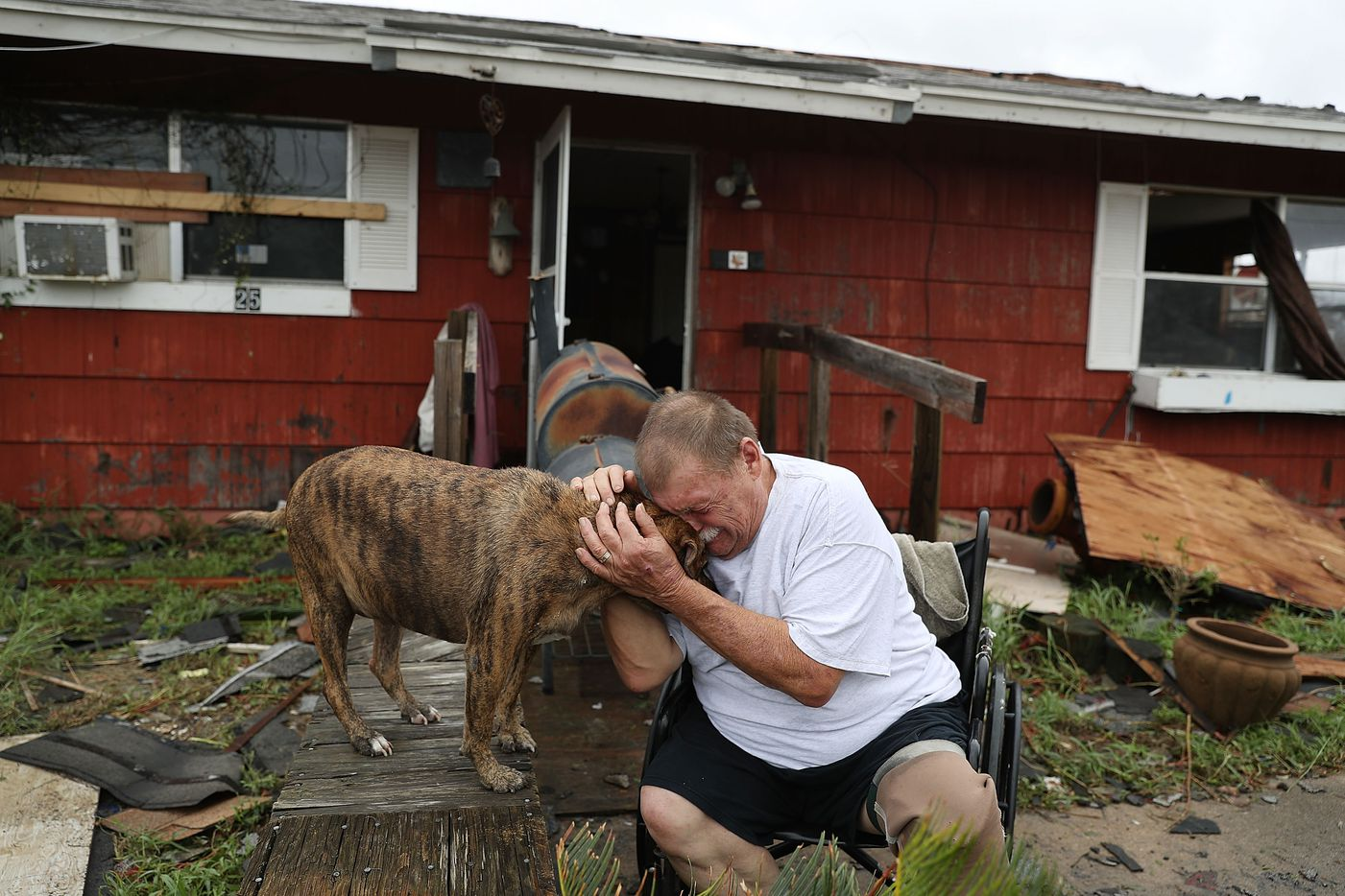 """Steve Culver cries with his dog Otis as he talks about what he said was the, """"most terrifying event in his life,"""" when Hurricane Harvey blew in and destroyed most of his home while he and his wife took shelter there on Saturday in Rockport."""