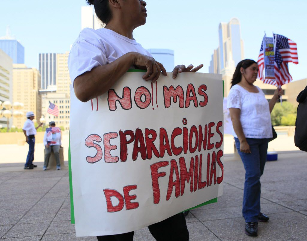 "A woman holds a sign that reads ""Stop separating families"" while listening to activists outside of Dallas City Hall during a march for immigration reform in May 2014."