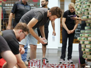 Ridgemont Construction's Zach Hanlon (center) places cans in the correct spot during the Canstruction charity event at NorthPark.