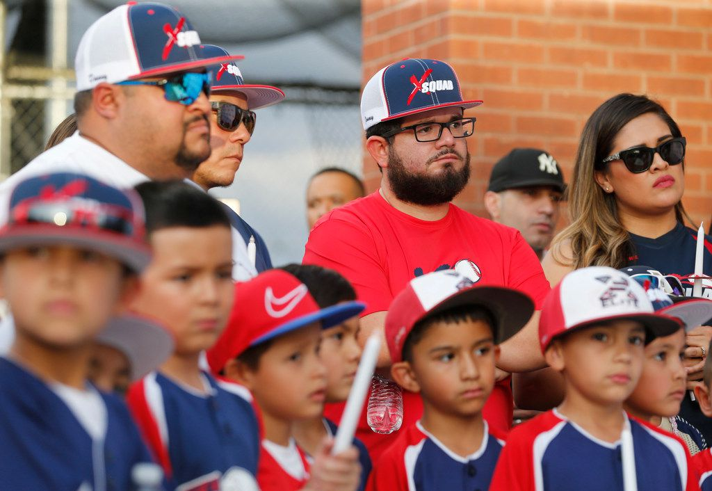 Danny Latin, Ray Garcia, and Jimmy Villatoro of El Paso listen during the candlelight vigil at The Sportspark in El Paso on Sunday, Aug. 4, 2019.