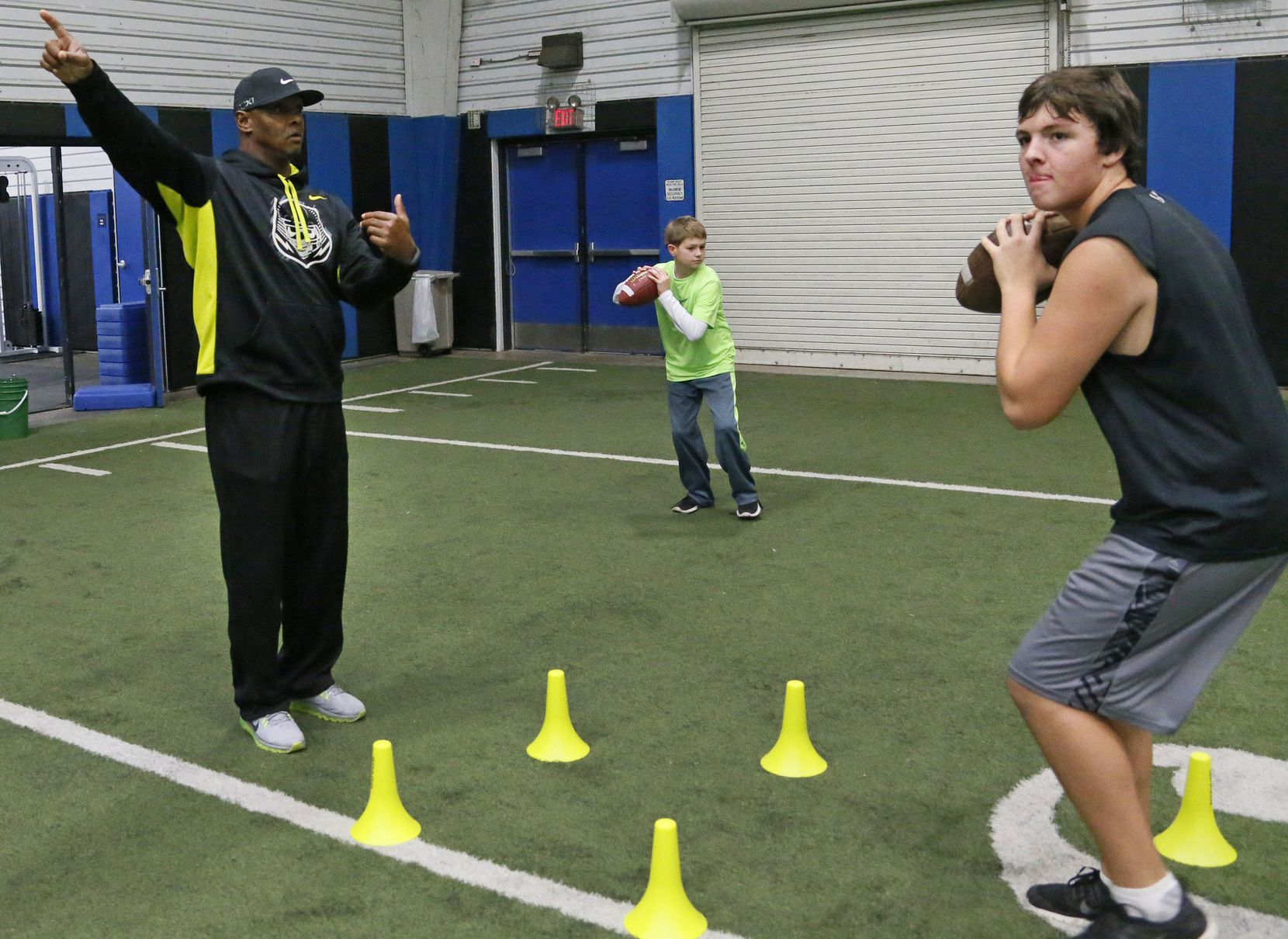 Former Texas A&M quarterback Kevin Murray works as a quarterbacks coach with 16-year-old Zach Gibson, right, and 11-year-old Dylan Gibson at Plano West High School in Plano on Wednesday, November 13, 2013.
