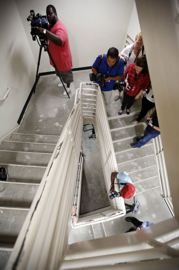 Photographers shoot pictures of the bullet-riddled walls and floor of the El Centro College stairwell, July 19, 2016, where the gunman escaped after killing four police officers in downtown Dallas. Part of the wall has been repaired (upper right). (Tom Fox/The Dallas Morning News)