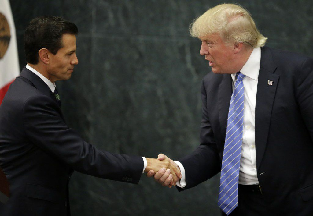 """(FILES) This file photo taken on August 31, 2016 shows Mexican President Enrique Pena Nieto (L) and US presidential candidate Donald Trump shaking hands after a meeting in Mexico City. Donald Trump said on November 9, 2016 he would bind the nation's deep wounds and be a president """"for all Americans,"""" as he praised his defeated rival Hillary Clinton for her years of public service. / AFP PHOTO / YURI CORTEZYURI CORTEZ/AFP/Getty Images"""